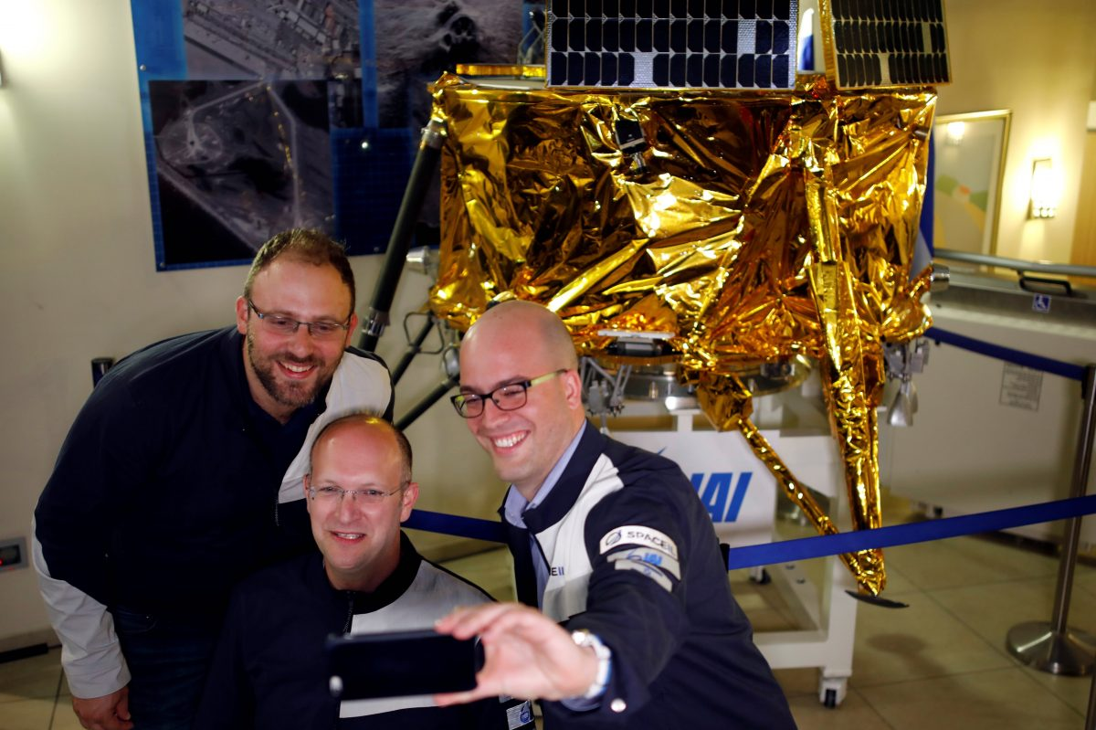 Members of Israeli non-profit group SpaceIL and representatives from Israel Aerospace Industries (IAI) do a selfie in front of a model of Beresheet spacecraft, near the control room, in Yahud
