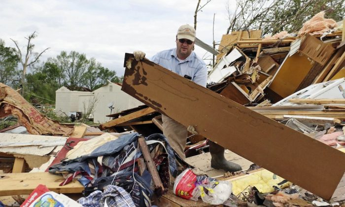 Roman Brown moves part of a wall out of his way as he looks for a friends medicine in their destroyed home along Seely Drive outside of Hamilton, Miss., after a storm moved through the area on April 14, 2019. (Jim Lytle/AP Photo)