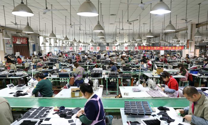 Employees work on the production line of a factory manufacturing fashion accessories in Sihong County, Jiangsu Province, China on March 27, 2019. (Reuters)