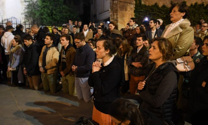 People kneel on the pavement as they pray outside watching flames engulf Notre-Dame Cathedral in Paris on April 15, 2019. (ERIC FEFERBERG/AFP/Getty Images)