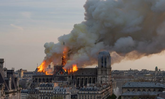 Smoke billows as flames burn through the roof of the Notre-Dame cathedral  in the French capital Paris on April 15, 2019. FABIEN BARRAU/AFP/Getty Images