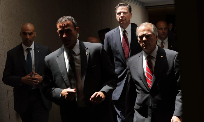 Former FBI Director James Comey (2R) moves from an open hearing to a closed hearing during a break in testimony before the Senate Intelligence Committee in the Hart Senate Office Building on Capitol Hill in Washington, DC. on June 8, 2017. (Chip Somodevilla/Getty Images)