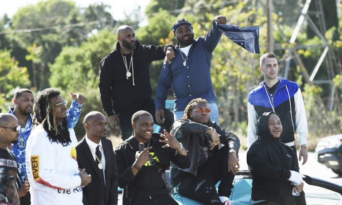 Friends and family attend the burial of late Rapper Nipsey Hussle at Forest Lawn Hollywood Hills Cemetery in Los Angeles, Calif., on April 12, 2019. (Chris Pizzello/Invision/AP)