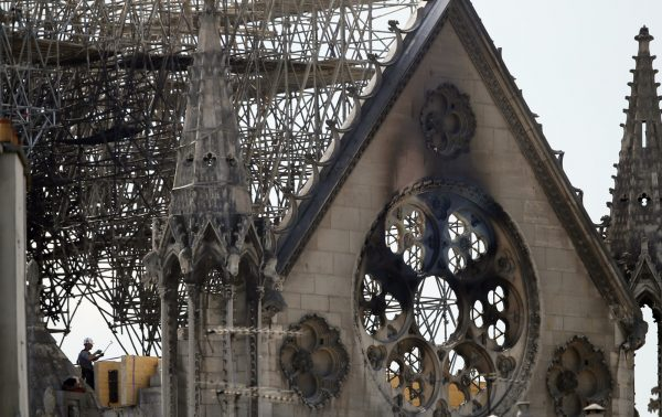 A worker checks on a wooden support structure placed on the Notre Dame Cathedral in Paris