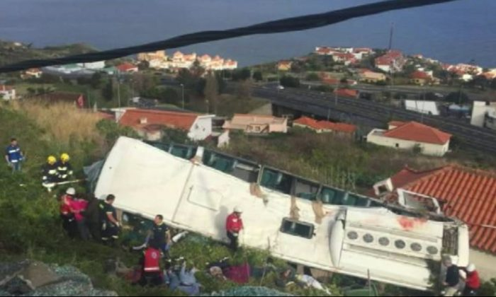 Emergency services attend the scene after a tour bus crashed at Canico, on Portugal's Madeira Island, on April 17, 2019. (TVI via AP)