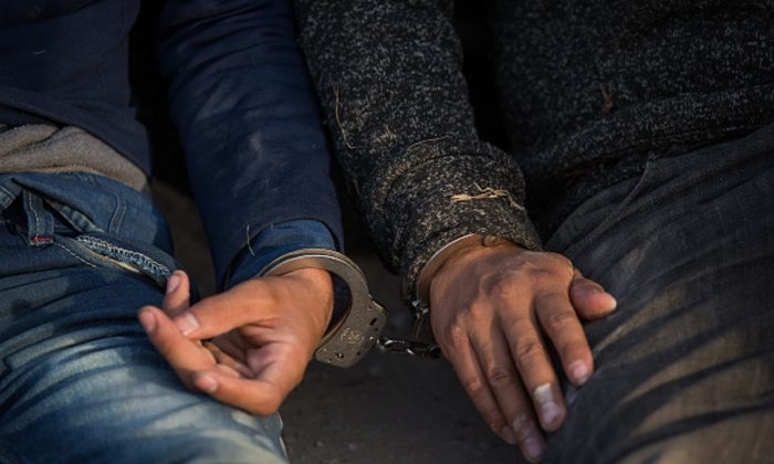 After being apprehended by Border Patrol, illegal immigrants wait to be transported to a central processing center shortly after they crossed the border from Mexico into the United States on Monday, in the Rio Grande Valley Sector near McAllen, Texas, on March 26, 2018. (Loren Elliott/AFP/Getty Images)