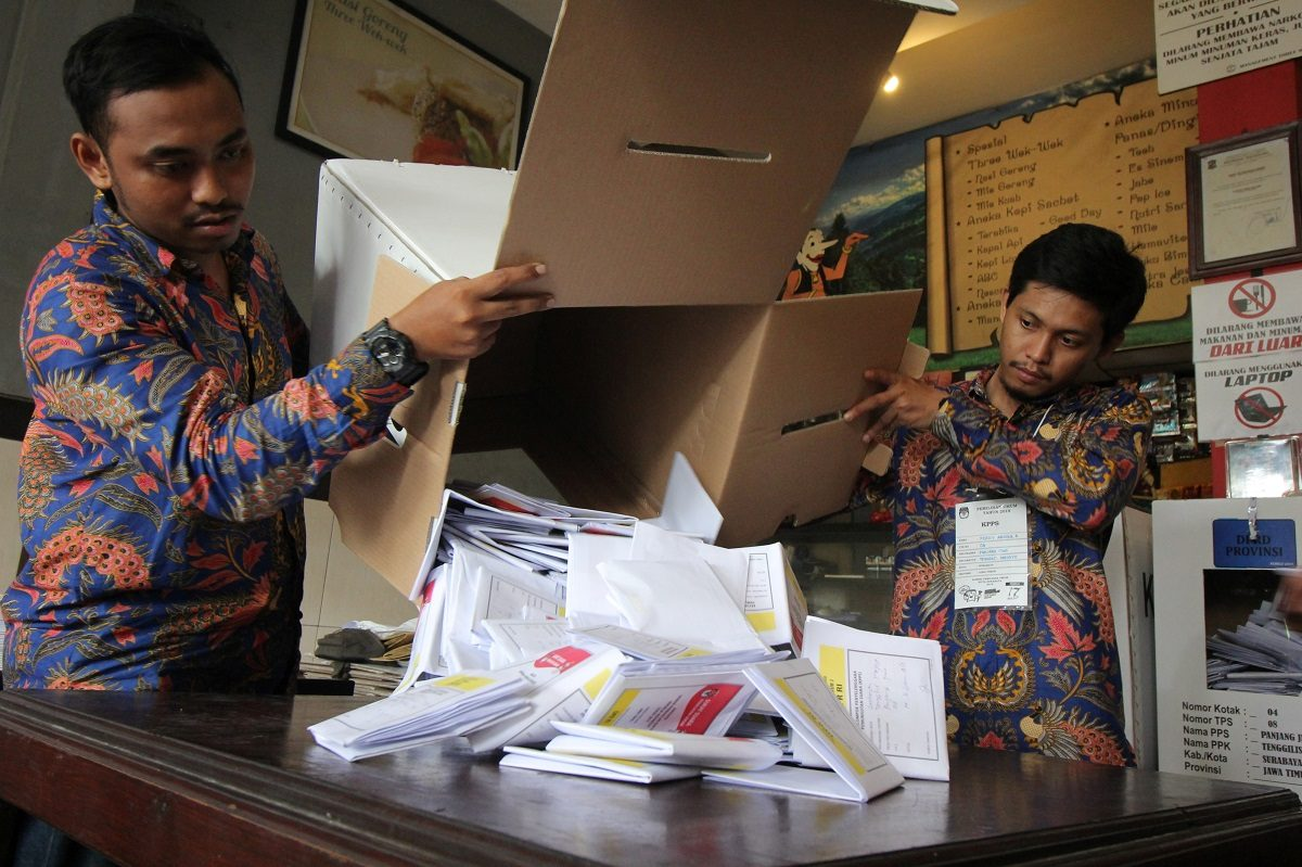 Electoral officials count ballots at a polling center