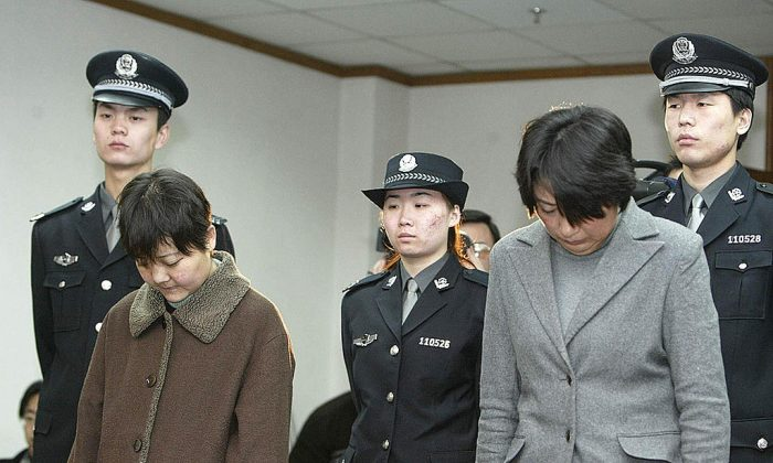 Police stand behind two defendants during a hearing at a Court in Beijing. (STR/AFP/Getty Images)