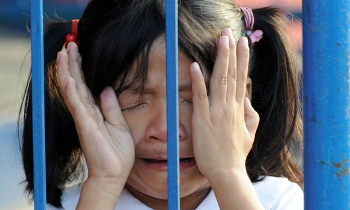 A girl crying behind a fence. (JAY DIRECTO/AFP/Getty Images)