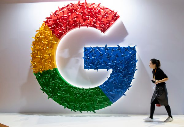 A woman passing a booth of Google