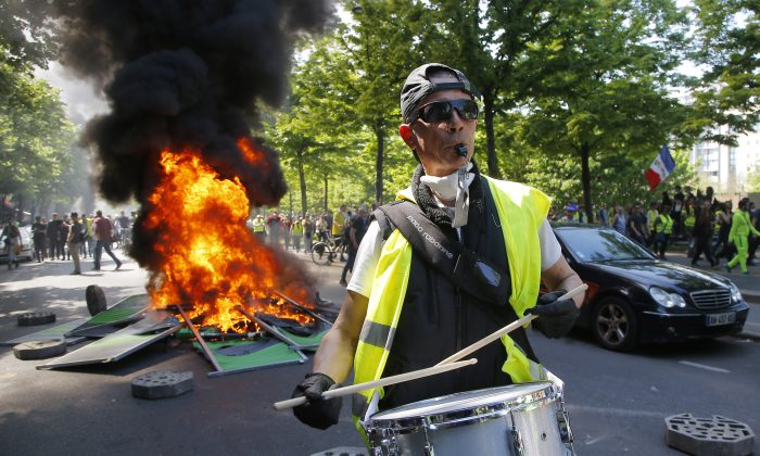 A man bangs a drum in front of a fire on the street during a yellow vest demonstration in Paris, on April 20, 2019.  (Michel Euler/AP Photo)