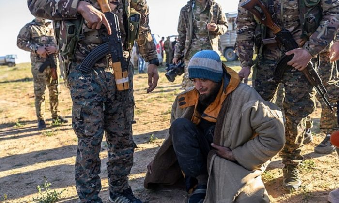 A man from Bosnia suspected of being an ISIS fighter is searched by members of the Kurdish-led Syrian Democratic Forces (SDF) after leaving the IS group's last holdout of Baghouz, in Syria's northern Deir Ezzor province on March 1, 2019. (Bulent Kilic/AFP/Getty Images)