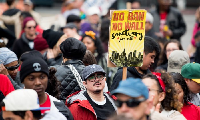 A man carries a sign supporting sanctuary cities during a march in Oakland, Calif., on Jan. 15, 2018. (Josh Edelson/AFP/Getty Images)
