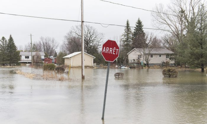 A residential street is shown surrounded by floodwaters in the town of Rigaud, Que. west of Montreal, on April 19, 2019. (Graham Hughes/The Canadian Press)