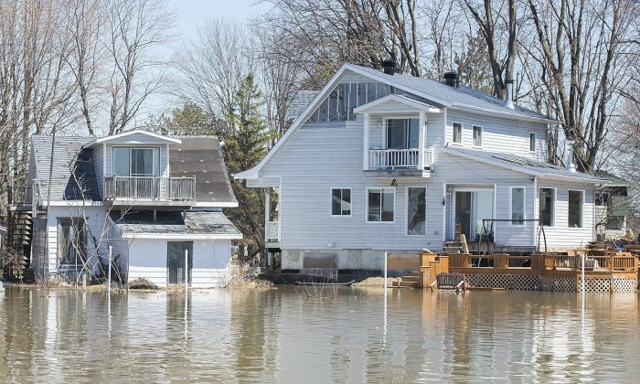 Homes surrounded by floodwaters are shown with a view from the Ottawa River in the town of Rigaud, Que., on April 22, 2019. (The Canadian Press/Graham Hughes)