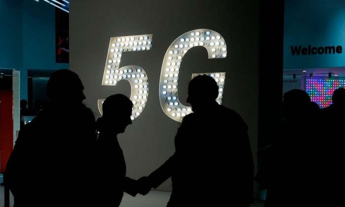 Visitors shake hands next to a 5G hotspot sign at the Mobile World Congress (MWC) in Barcelona on Feb. 27, 2019. (Pau Barrena/AFP/Getty Images)