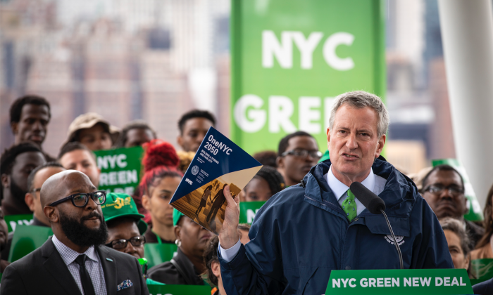 New York City Mayor Bill de Blasio holds up a copy of 'One NYC 2050' as he speaks about the city's response to climate change at Hunters Point South Park in the Queens borough of New York City on April 22, 2019. (Drew Angerer/Getty Images)