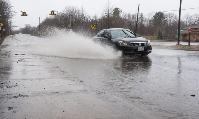 Streets and sidewalks are flooded from heavy rain on Foresthill Road in Fredericton, N.B. on Saturday, April 20, 2019. (The Canadian Press/Stephen MacGillivray)