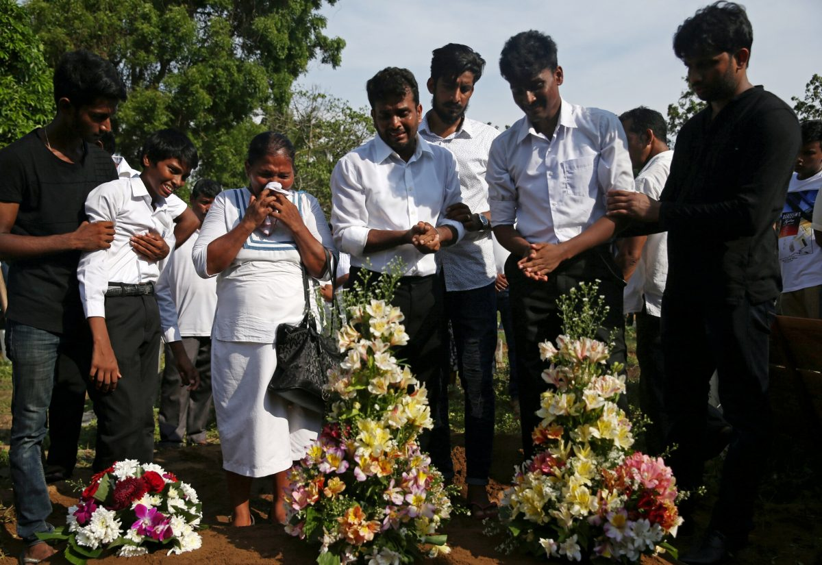 People react during a mass burial of victims