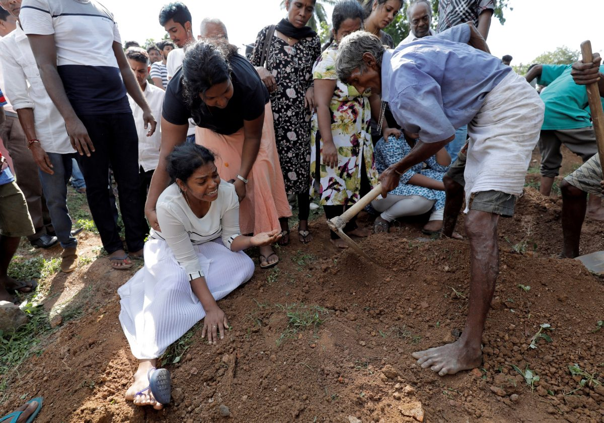 A woman reacts during a mass burial of victims