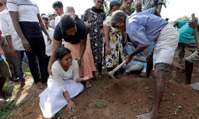 A woman reacts during a mass burial of victims, two days after a string of suicide bomb attacks on churches and luxury hotels across the island on Easter Sunday, in Colombo, Sri Lanka, on April 23, 2019. (Dinuka Liyanawatte/Reuters)