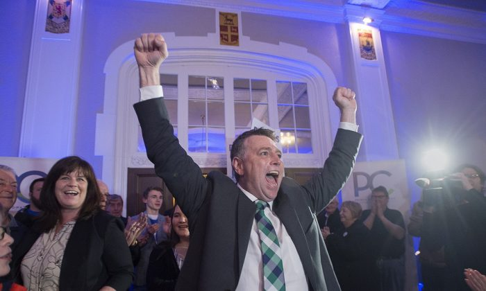 Progressive Conservative leader Dennis King, accompanied by his wife Jana Hemphill, left, arrives to greet supporters after winning the Prince Edward Island provincial election in Charlottetown on April 23, 2019. (Andrew Vaughan/The Canadian Press)