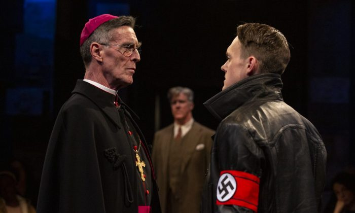 A difference of opinion: Bishop von Galen (John Glover, L) opposes the National Socialist German Workers Party policies enforced by the deputy director of a clinic for disabled children (Sam Lilja), while the clinic's doctor, Dr. Victor Franz (Karl Kenzler) looks on. (Maria Baranova)