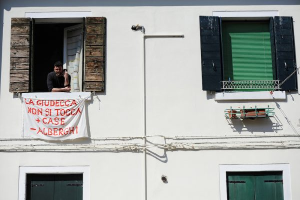 Alessandro Dus, 34, talks on the phone in his illegally occupied apartment in the Casette neighbourhood in Venice