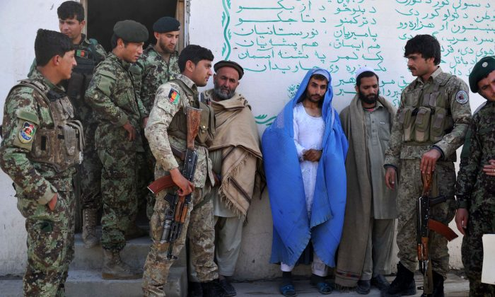 Afghan security personnel present a burqa-clad resident they say is a Taliban fighter to the Afghan National Army headquarters in Khogyani District near Jalalabad on March 18, 2014. (Noorullah Shirzada/AFP/Getty Images)