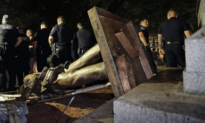 Police stand guard after the Confederate statue known as Silent Sam was toppled by protesters on campus at the University of North Carolina in Chapel Hill, N.C. ,on Aug.20, 2018. (Gerry Broome, AP Photo/File)