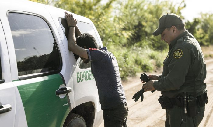 A Border Patrol agent prepares to search an illegal alien from Mexico who tried to evade capture after crossing the Rio Grande into the United States near McAllen, Texas, on April 18, 2019. (Charlotte Cuthbertson/The Epoch Times)