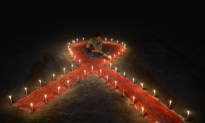 An person lights candles forming the shape of a ribbon as part of World AIDS Day in Siliguri, West Bengal, India, on Dec. 1, 2018. (Diptendu Dutta/AFP/Getty Images)
