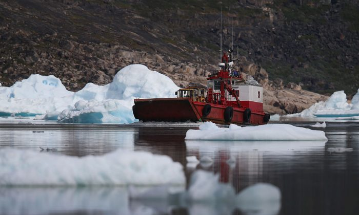 A boat navigates among calved icebergs from the nearby Twin Glaciers in Qaqortoq, Greenland, on July 21, 2013. (Joe Raedle/Getty Images)