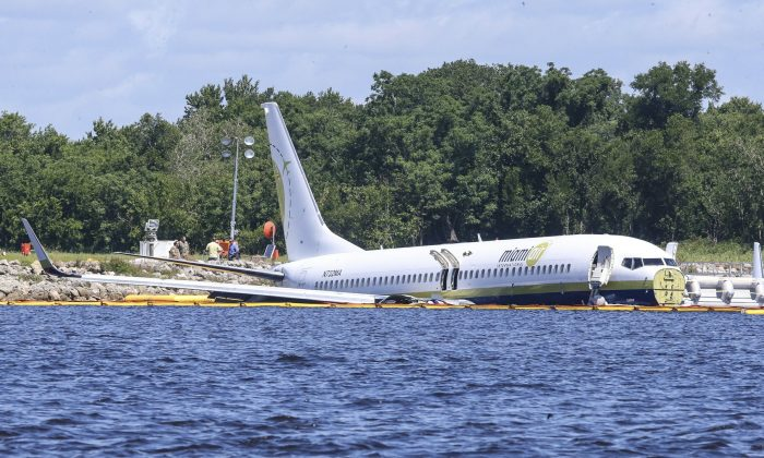 A Miami Air International charter plane sits at the end of a runway in a river at Jacksonville, Fla., on May 4, 2019. (AP Photo/Gary McCullough)