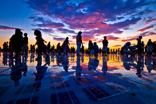 people silhouetted in sunset over zadar sun salutation