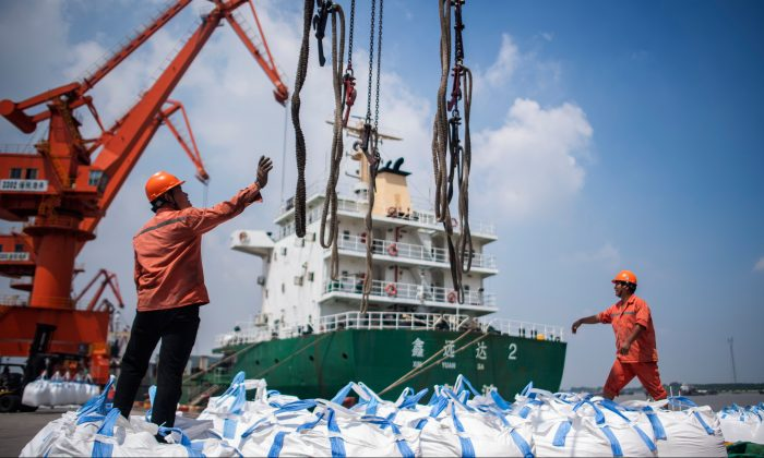 Workers unload bags of chemicals at a port in Zhangjiagang in China's eastern Jiangsu province on Aug. 7, 2018. (Johannes Eisele/AFP/Getty Images)