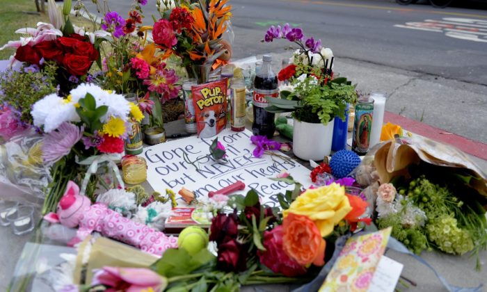 Photo flowers and cards rest on a memorial for Jessica Bingaman on May 8, 2019, a popular dog walker, who was killed along with five of six dogs she was transporting in Long Beach, Calif. (Brittany Murray/The Orange County Register via AP)