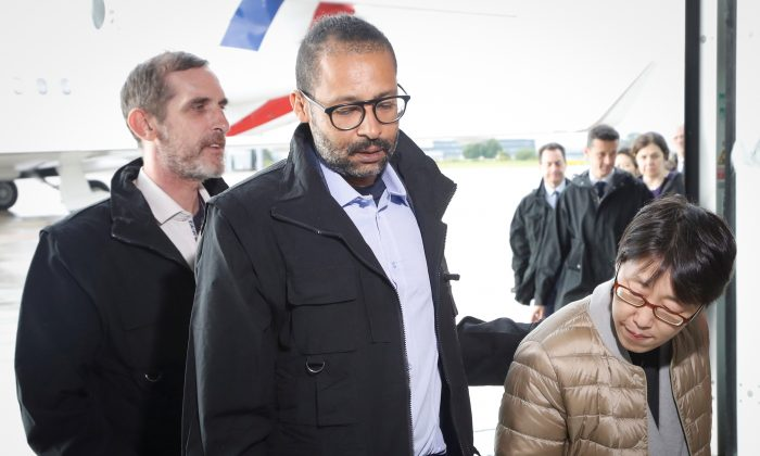 Freed French hostages Patrick Picque and Laurent Lassimouillas walk alongside a South Korean hostage upon their arrival at the Villacoublay airport, in Velizy-Villacoublay, France on May 11, 2019. (Francois Guillot/Pool via Reuters)