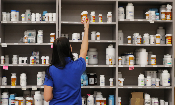 A pharmacy technician grabs a bottle of drugs off a shelf, on Sept. 10, 2018, in Midvale, Utah. (George Frey/Getty Images)