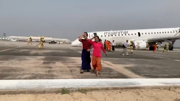 Passengers walk away from the plane after Myanmar National Airlines flight UB103 landed without a front wheel at Mandalay International Airport in Tada-u