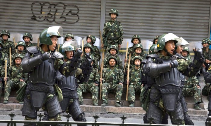 Chinese paramilitary police practice during a break from patrol in Urumqi, western China's Xinjiang province, in a file photo. China's rights violations and use of technology to spy on people at home and abroad were the topic of a panel discussion hosted by the Canadian International Council in Ottawa on May 8, 2019. (AP Photo/Ng Han Guan, File)
