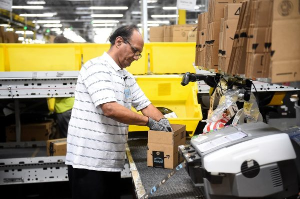 Packing worker Hashmat Zubair fills a delivery box with products at the Amazon fulfillment center