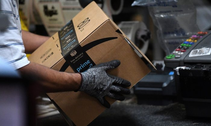 A worker assembles a box for delivery at the Amazon fulfillment center in Baltimore, Md., on April 30, 2019. (Clodagh Kilcoyne/Reuters)