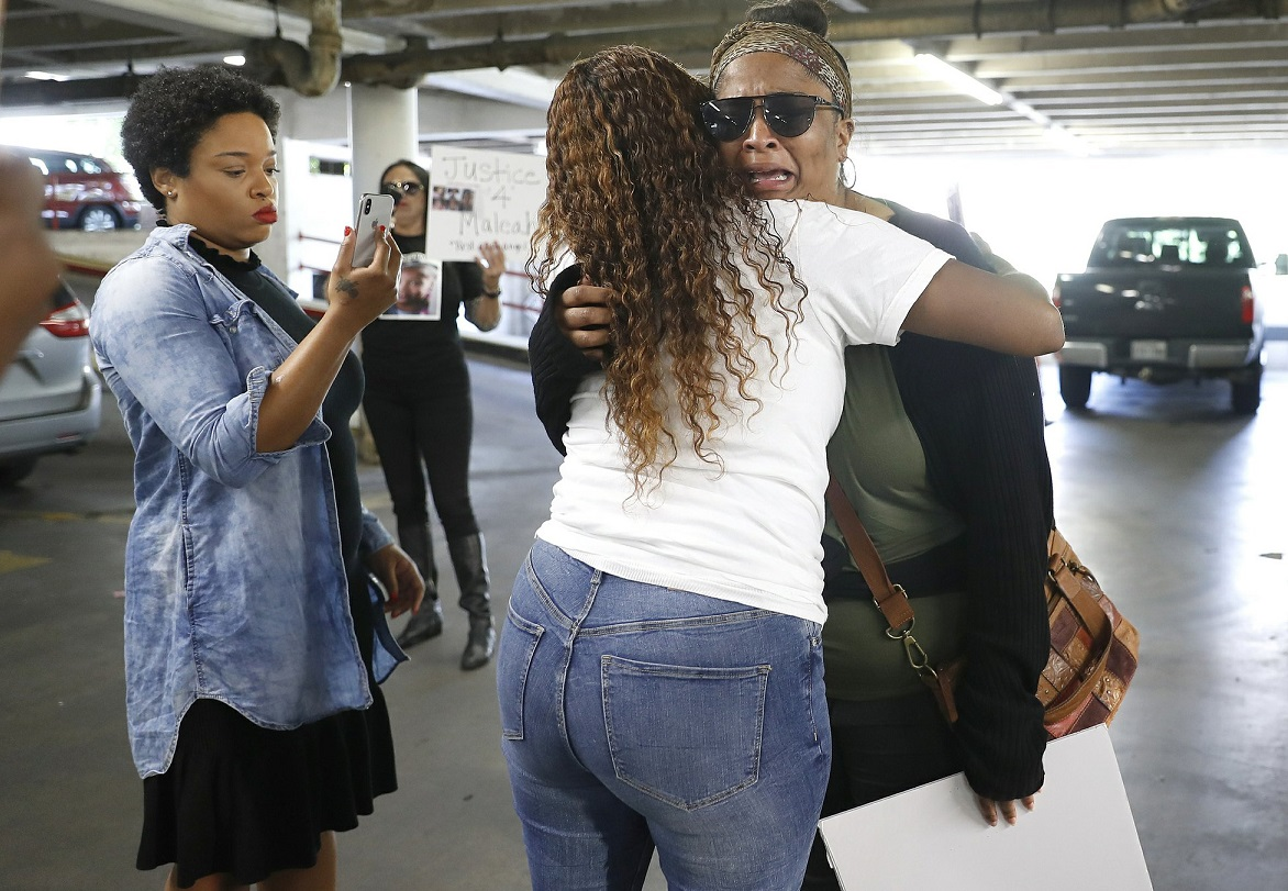 Brittany Bowens, facing camera, the mother of the missing 4-year-old, Meleah Davis is hugged by Taneshia Brown,