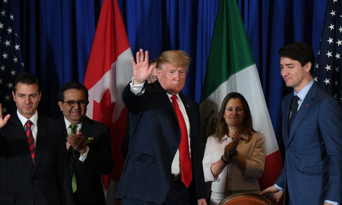 U.S. President Donald Trump (C) waves next to Mexican President Enrique Pena Nieto (L),  Mexican Economy Minister Ildefonso Guajardo (2-L) Canadas Foreign Affairs Minister Chrystia Freeland (2-R) and Canadian Prime Minister Justin Trudeau, after signing a new free trade agreement in Buenos Aires, on Nov. 30, 2018. MARTIN BERNETTI/AFP/Getty Images