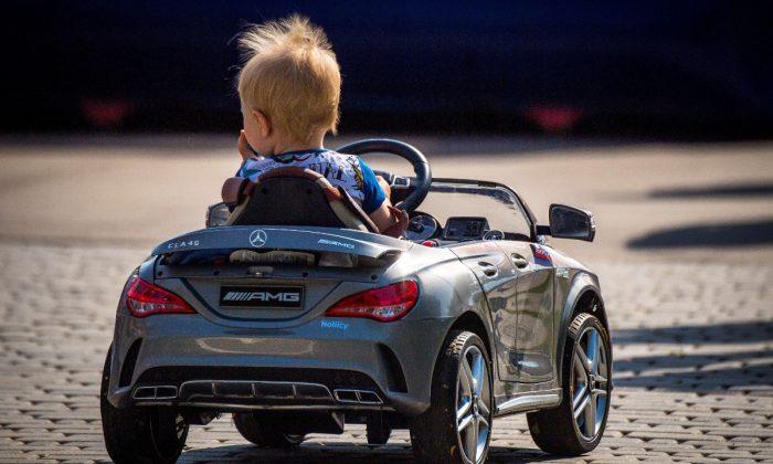 A boy in a toy car. (Mladen Antonov/AFP/Getty Images)