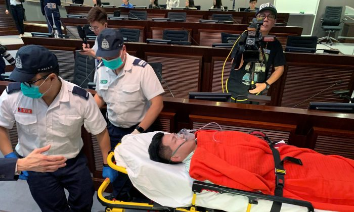 Pro-democracy lawmaker Gary Fan is carried away on a stretcher after clashes with pro-Beijing lawmakers during a meeting for control of a meeting room to consider the controversial extradition bill, in Hong Kong, China on May 11, 2019. (James Pomfret/Reuters)