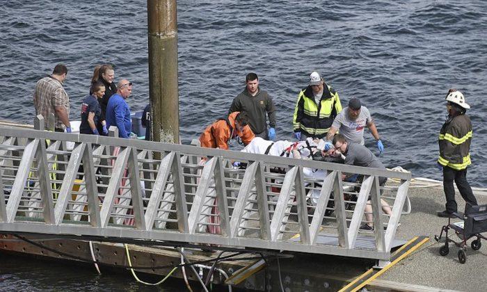 Emergency response crews transport an injured passenger to an ambulance at the George Inlet Lodge docks, in Ketchikan, Alaska on May 13, 2019. (Safranek/Ketchikan Daily News via AP)