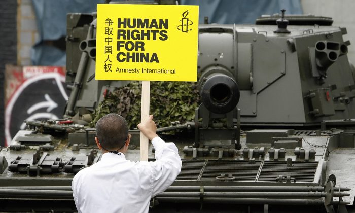 """A man stands in front of a tank outside Amnesty International's headquarters in London on June 3, 2008 to recreate the """"tank man"""" image of a lone demonstrator facing down tanks at Tiananmen Square. The anniversary of the 1989 crackdown against pro-democracy protesters in Beijing is on June 4. (Leon Neal/AFP/Getty Images)"""