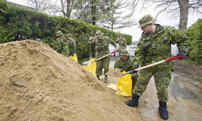 Soldiers from the Canadian Army help with cleanup operations in the Quebec flood zones. (Graham Hughes/The Canadian Press)